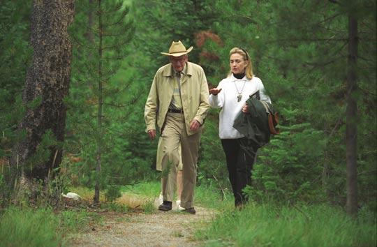 Hillary Rodham Clinton loopt in druk gesprek met Laurance Rockefeller op diens ranch.