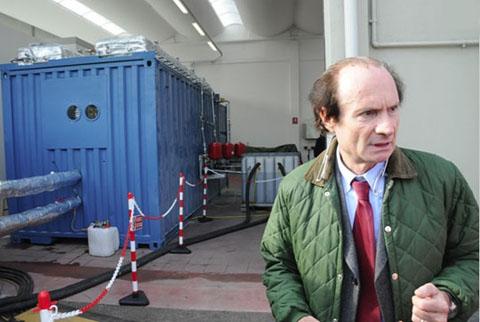 .Andrea Rossi met achter hem, in de blauwe container, de eerste 'E-cat'-proefgenerator voor industrieel gebruik.